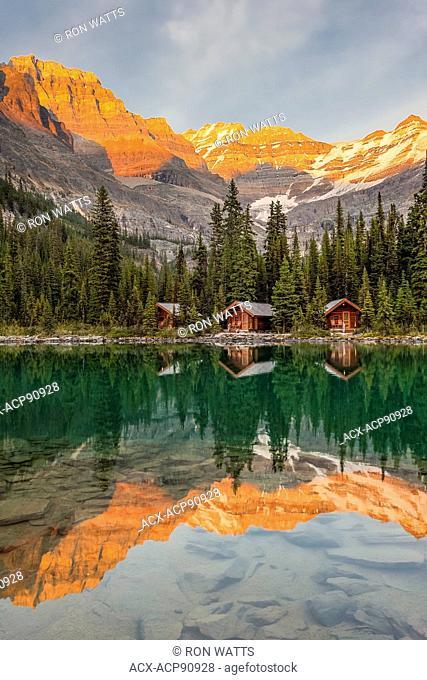 Lake O'Hara Lodge guest cabins are reflected in the calm lake at sunset. Lake O'Hara, Yoho National Park, British Columbia Canada