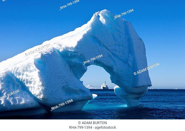 Looking through an Antarctic iceberg arch to the Akademik Ioffe research ship on the horizon, Antarctica, Polar Regions