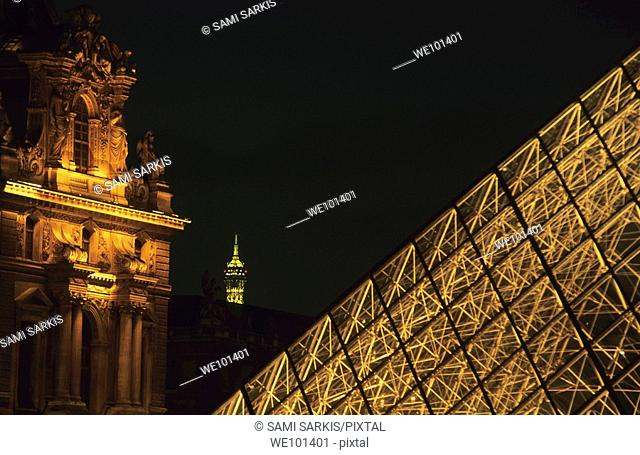 The Louvre Pyramid illuminated at night, with the tip of the Eiffel Tower in the distance, Paris, France