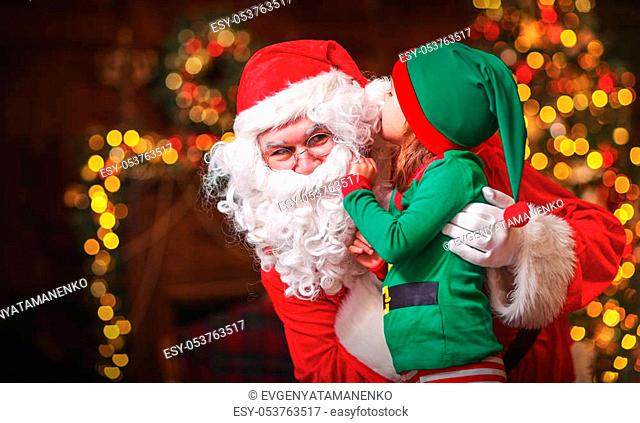 happy cheerful child elf helper in the hands of Santa Claus at Christmas