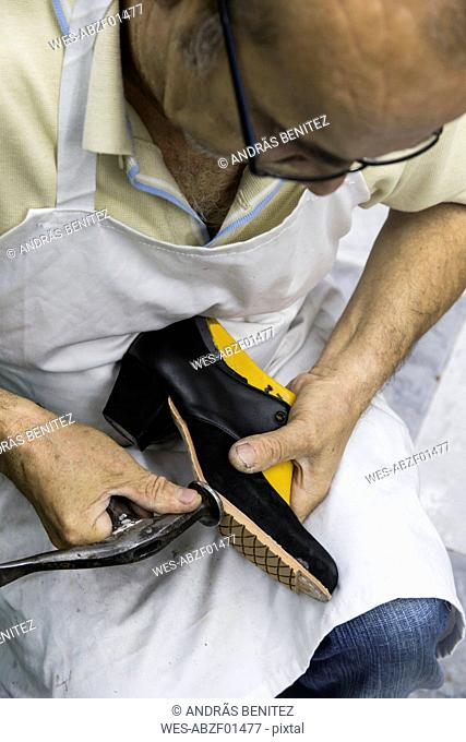 Shoemaker working with hammer on shoe in his workshop