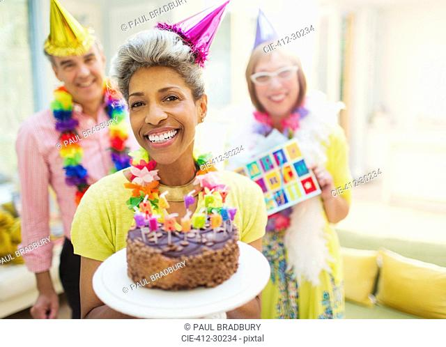 Portrait smiling mature woman holding chocolate birthday cake with friends in background