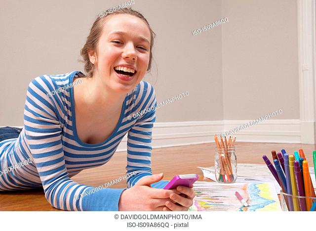 Girl lying on floor with smartphone and art materials