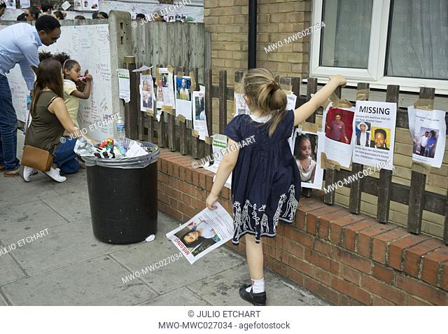 Visitors writing notes of condolence for victims of the fire disaster at the Grenfell Tower in London, England, UK