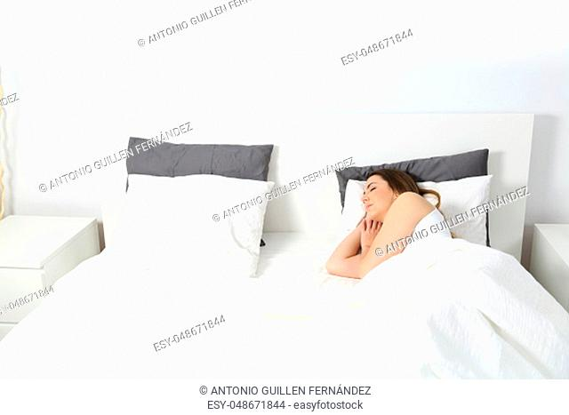 Wide angle view of a woman sleeping in a bed at home with an isolated white wall in the background above