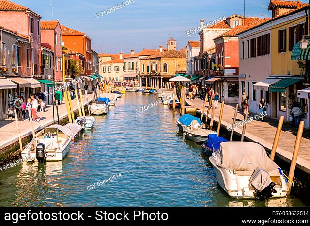 Murano Venice, Italy - October 29, 2016: View of the central canal on Murano island in Venice Italy. The canal is surrounded with tourist shops selling the...