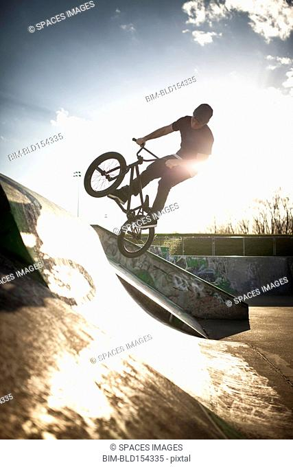 Caucasian man riding BMX bicycle at skate park