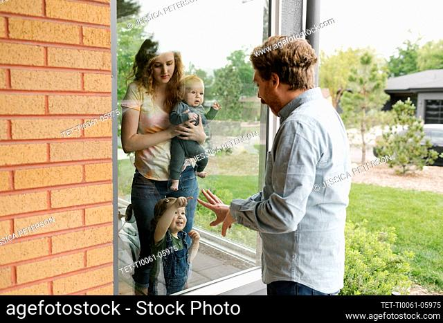 USA, Utah, Salt Lake City, Father visiting partner and children (6-11 months, 2-3) through window