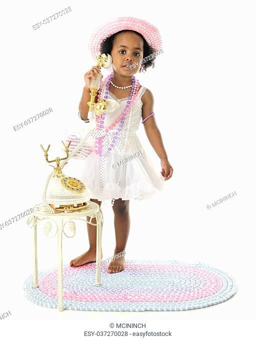 An adorable 2 year old diva calling the viewer to her fancy French phone. She wears a white slip and petticoat, and pastel hat and beads