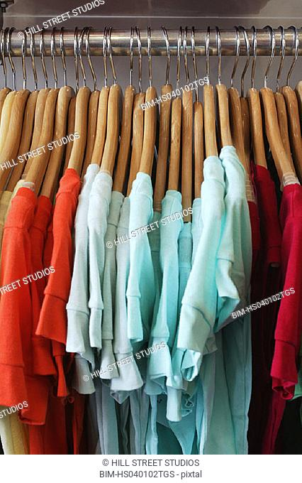 T-shirts on hangers sorted by color