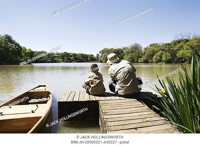 Father and son sitting on dock