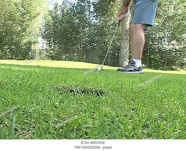 A golfer putts the ball into the cup
