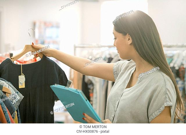 Fashion buyer with digital tablet looking at shirt