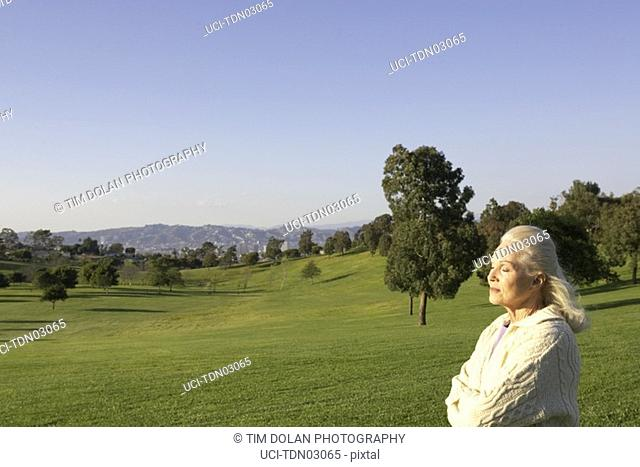 Senior woman standing in meadow