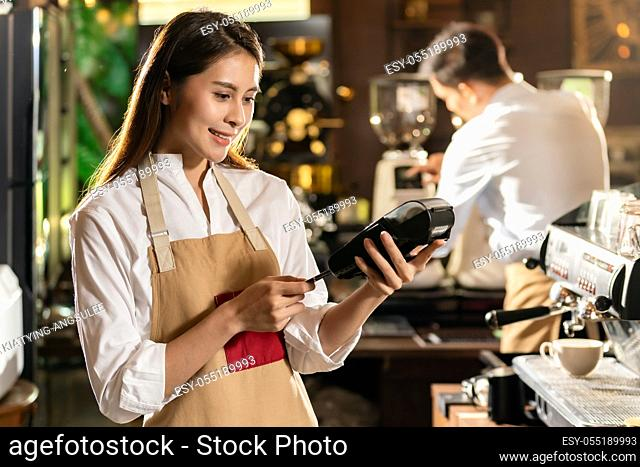 Asian Barista make payment with customer credit card using EMV chip technology for coffee purchase at a cafe bar