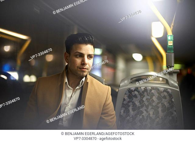 young man alone in bus next to empty seat, in Berlin, Germany