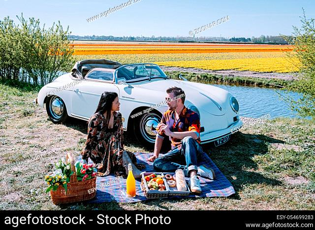 Lisse Netherlands , . couple doing a road trip with a old vintage sport car White Porsche 356 Speedster, Dutch flower bulb region with tulip fields