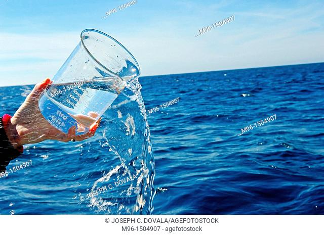 Pouring sea water from beaker on ocean