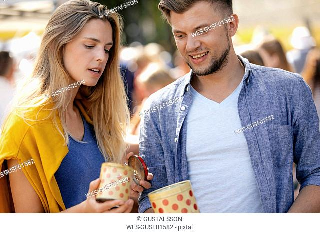 Belgium, Tongeren, young couple with tin cans on an antique flea market