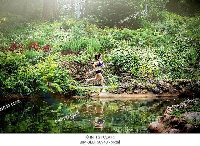 Caucasian woman running near lake in park