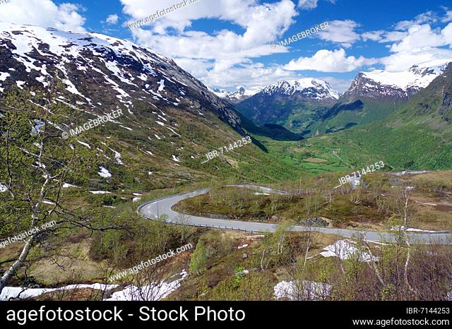 Road winds up the mountain, remnants of snow and mountain peaks, mountain pass and fjord, Geiranger, Norway, Europe
