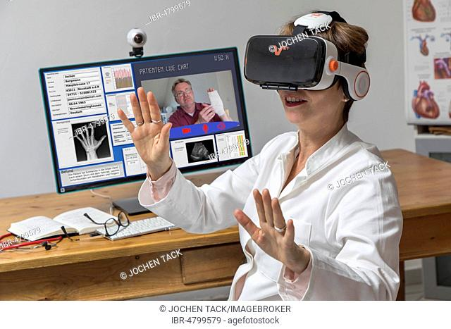 Symbol photo for telemedicine, doctor in a practice, with VR glasses, Virtual Reality, 3-D presentation of an MRT result