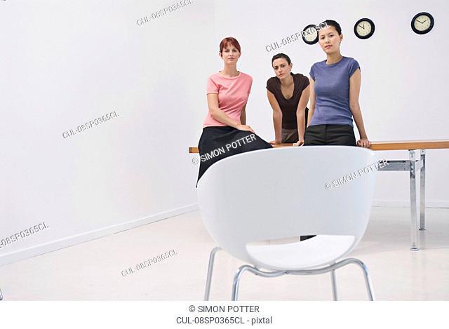 Business women sitting on a desk