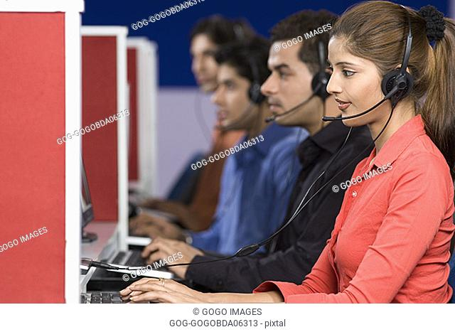 Businesspeople wearing headsets while working at computers