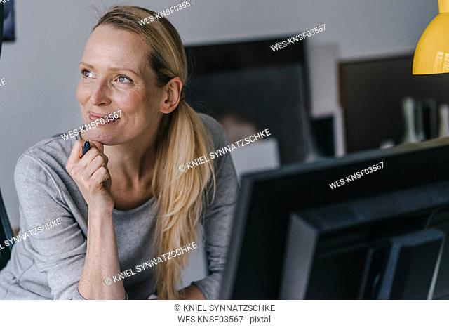 Smiling woman sitting at desk thinking