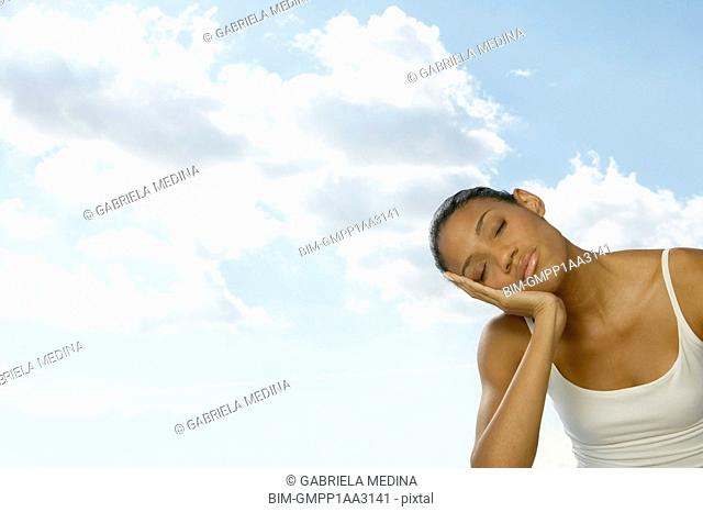African woman with eyes closed leaning head in hand