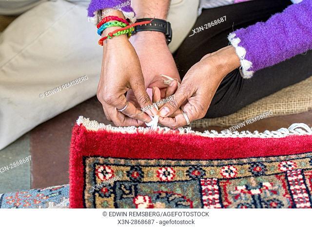 Jaipur, India - Hands weaving threads on oriental rug