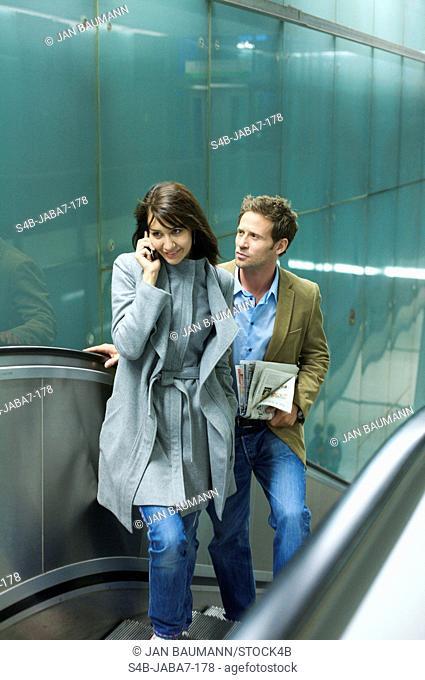 Man and woman on escalator, Munich, Bavaria, Germany