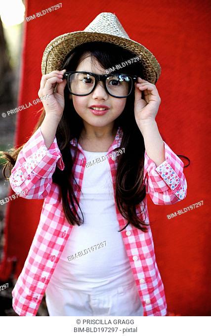 Mixed race girl in hat adjusting eyeglasses