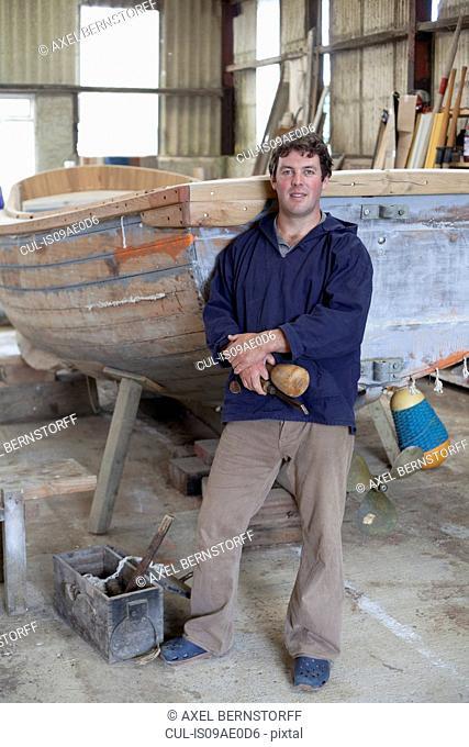 Portrait of mature man holding chisel in boat workshop
