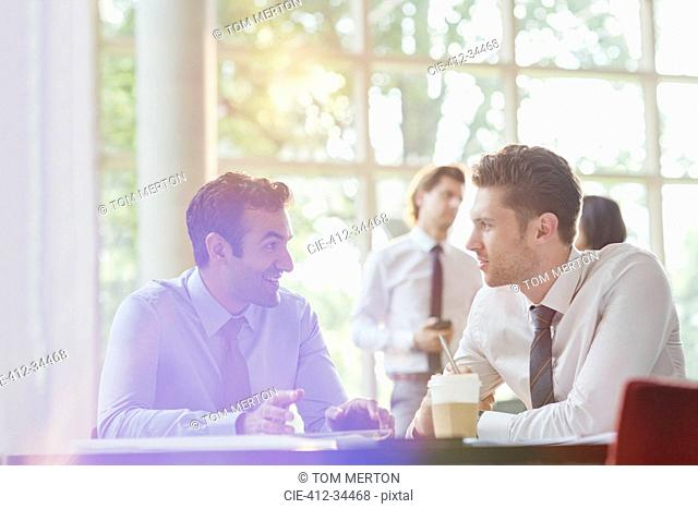 Businessmen drinking coffee and talking in office meeting