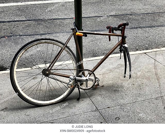 New York City, Manhattan. Bicycle Secured with a Lock to a Post, Front Tire Missing Anyway