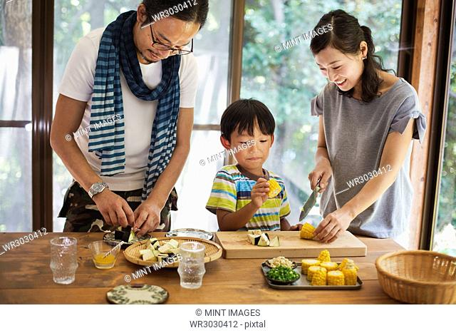 Man, woman and boy standing at a table, preparing corn on the cob, smiling