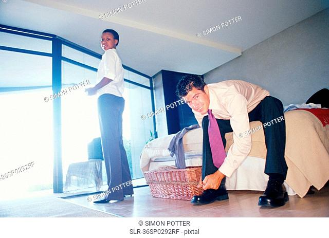 Couple getting ready for work in bedroom