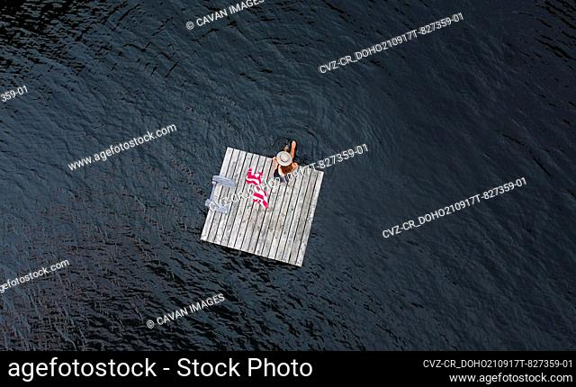 Aerial of woman sitting alone on floating dock on lake in summer
