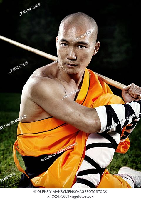 Portrait of a Shaolin warrior monk in a Kung Fu stance with a staff