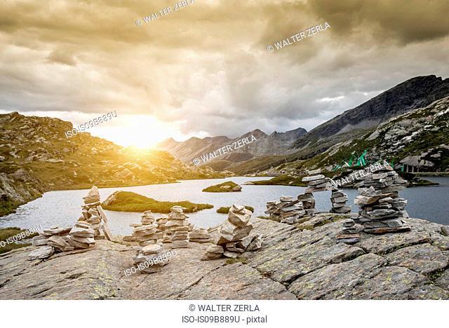 Stacks of rocks by lake at sunset, San Bernardino, Ticino, Switzerland, Europe