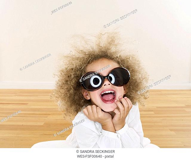 Portrait of smiling girl with blond ringlets wearing oversized sunglasses