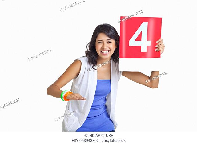 Portrait of happy young female signaling four over white background