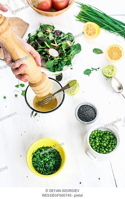 Hand preparing a salad seasoning with pepper