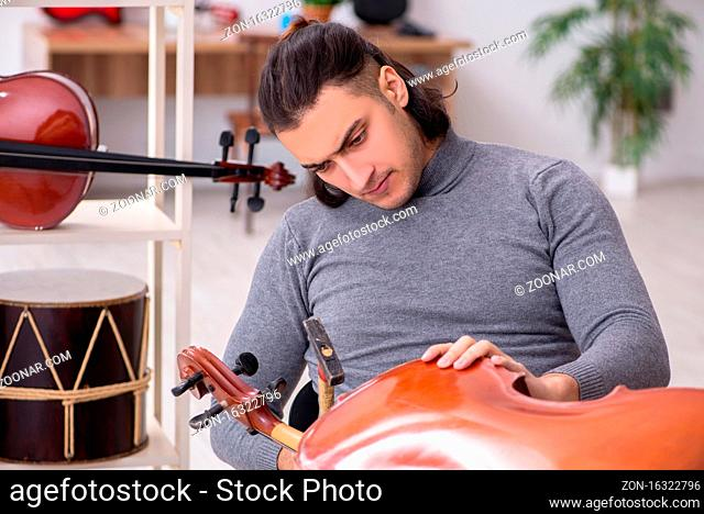 Young male repairman repairing cello in workshop