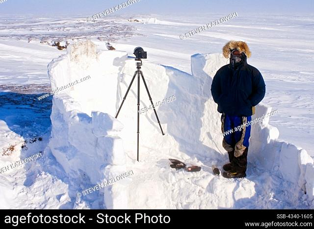 Inupiaq guide stands inside an igloo snow blind used to photograph a polar bear den along the Arctic coast of Alaska in early spring
