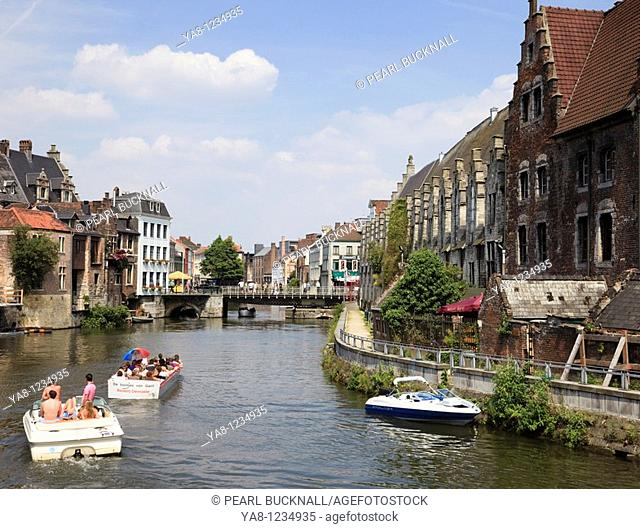 Graslei Site, Ghent, East Flanders, Belgium, Europe  Tourists in sightseeing cruise boats on the River Leie lined with medieval Flemish quayside guild houses in...