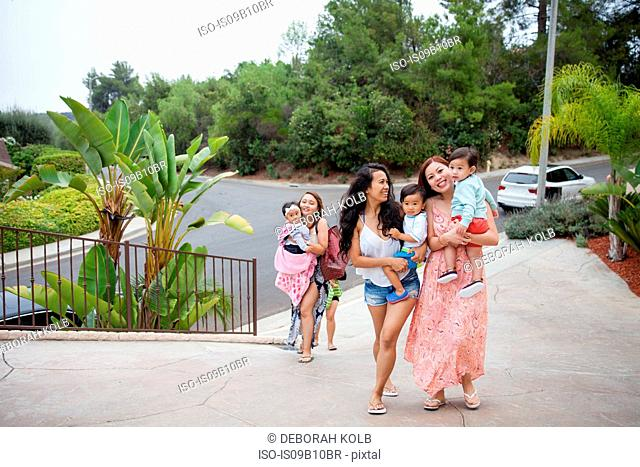 Women carrying baby daughter and sons moving up driveway, Malibu, California, USA