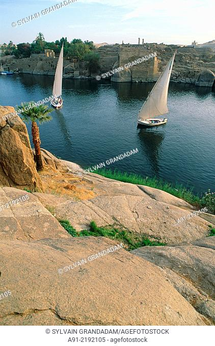 EGYPT.NUBIA.ASWAN.TWO FELUCCAS ON THE NILE.RED ROCKS AT FORE