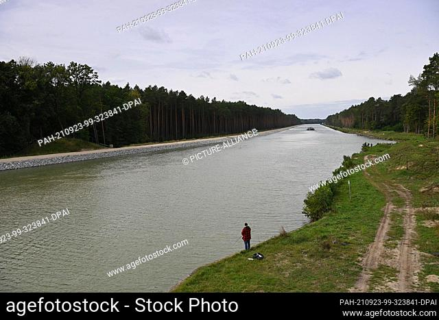 21 September 2021, Brandenburg, Schorfheide: An angler stands on the bank of the Oder-Havel Canal. The canal is currently being widened to 55 metres and made...